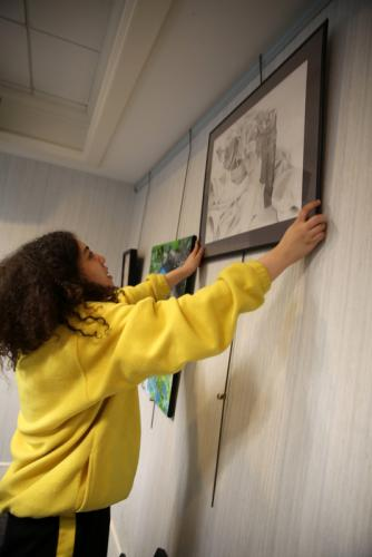 NHS junior Danielle Wassmer hangs one of her six pieces of artwork on December 21 in the Meeting Room at C.H. Booth Library. Danielle is one of seven students with artwork on display. (Bee photo, Hallabeck)