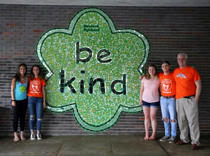 Newtown High School Student Government Co-Presidents, from left, Hana Rosenthal, Justice Zoto, Annika Brady, and Connor Munro stand with Student Government advisor Larry Saladin next to the school's freshly finished Ben's Bells mural, on June 1. …