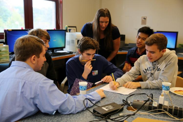 NHS computer science teacher Kristin Violette looks on as one group of students works to solve a problem at the NHS Puzzle Day on October 13. Students pictured from left are Connor Parsons, Will Gregorio, Thomas Hartley, Youmeng Hin, and Ardit…