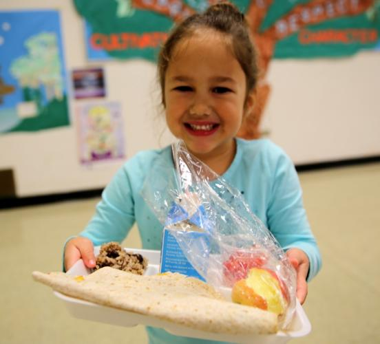 Head O' Meadow kindergartener Adrianna Feder holds up her lunch of a quesadilla, rice and beans, and an apple served on November 16.  (Bee Photo, Hallabeck)