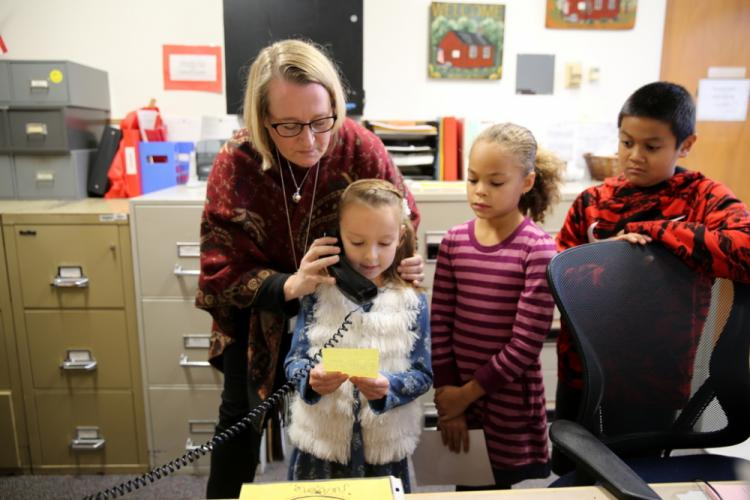 Middle Gate third grade teacher Leanne Connors helps student Anna Vereshagin share a message in Russian during the morning announcement at the school on November 17, as students Brynn Lozer and Ryan Yong, right, look on. (Bee Photo, Hallabeck)