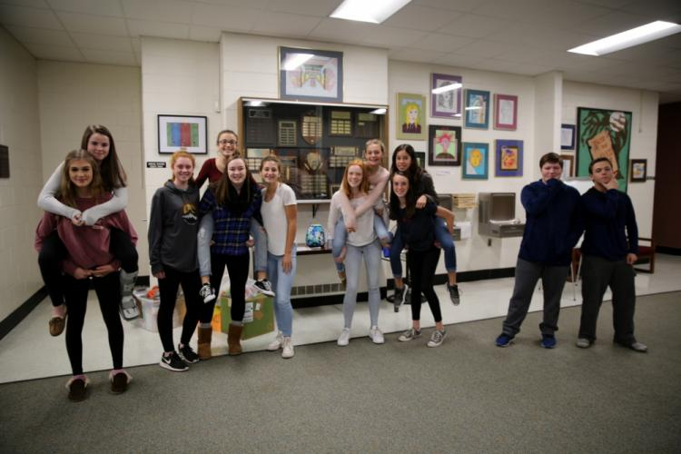 Student group members in this year's Eighth Grade Scarecrow Contest show their excitement and creativity when announcing the charities that will receive their winnings. Groups members pictured from left are, Tessa Bigwarfe carrying Elena Sughrue;…