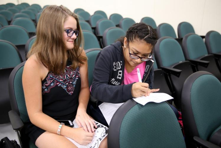 Newtown Middle School eighth graders Kendall Reed, left, and Katherine Rodriguez work together to fill out a form to submit an idea for their scarecrow. (Bee Photo, Hallabeck)