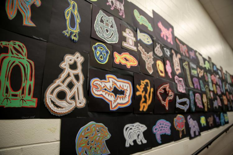 """""""Cut-Paper Molas"""" created by eighth grade students were on display along one wall at NMS. According to a description for the lesson, """"Students did research to discover what their spirit animal was, and set out to create a mola inspired by the women…"""