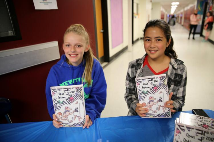 Newtown Middle School seventh graders Jessica D'Amico, left, and Sarah Adams hold copies of the school's literary magazine Opus Optima, which were on sale at the April 25 Student Showcase. (Bee Photo, Hallabeck)