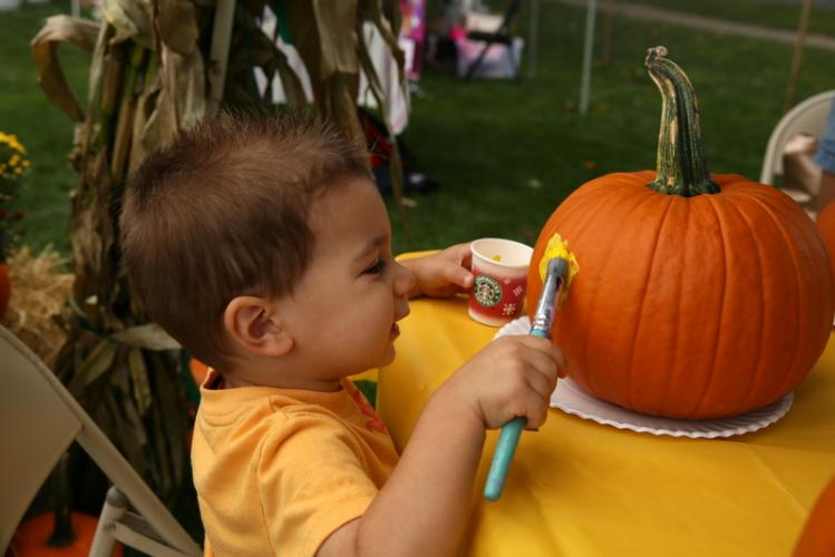Mason Kisker, 2, paints a pumpkin at a Newtown High School Marching Band & Color Guard booth. The activity was a fundraiser for the Color Guard. (Bee Photo, Hallabeck)
