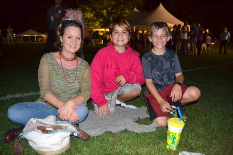 Stephanie Barnes, Juliano Barnes, center, and Nick D'Amico sit together at Friday's evening concert. (Bee Photo, Hallabeck)