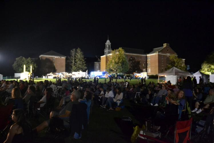Audience members at the concert on Friday evening were lit partially by the food trucks lined up on the side of the field. (Bee Photo, Hallabeck)