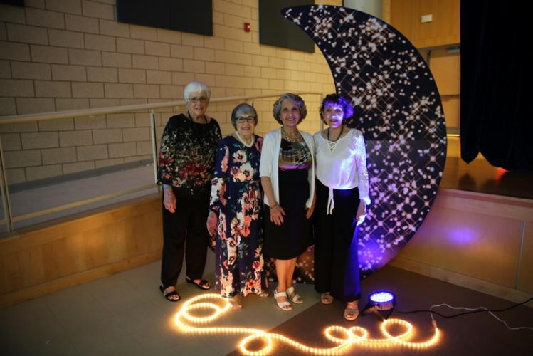 A glimmering moon beams over the shoulders of, from left, Mary Maday, Rose West, Marianne Corbo, and Marianne Muskus at the Newtown Parks & Recreation Senior Citizen Prom event at Newtown High School.  (Bee Photo, Hallabeck)