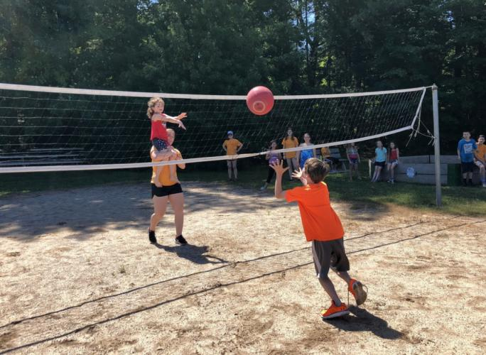 Parks & Recreation Day Camp staff member Brianna Baranowski carries camper Bernadette Biasetti as she sends a ball over the net to camper Brian Shepard during a volley ball game on June 29. (Bee Photo, Hallabeck)