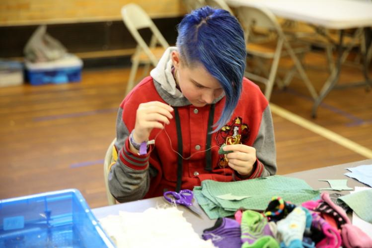 Treasa L'Sullivan makes a cat toy at one table of the fundraising event. (Bee Photo, Hallabeck)