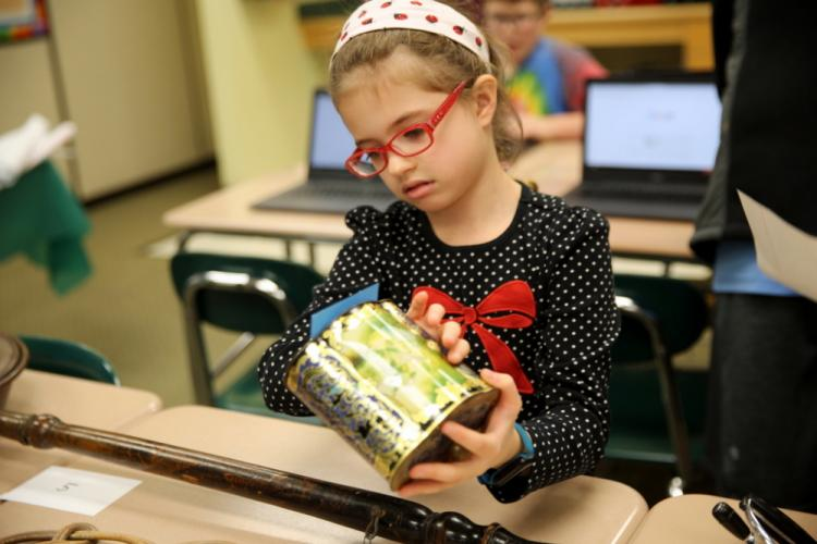 Reed fifth grader Ella Renak inspects an item at the Hands On History TAGtivity to determine what it was used for. (Bee Photo, Hallabeck)
