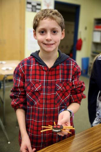 """Reed sixth grader Nathaniel Lewis holds his spider snack, made from Oreo cookies and pretzels, at the """"Creature Feature Cooking"""" TAGtivity on November 1. (Bee Photo, Hallabeck)"""