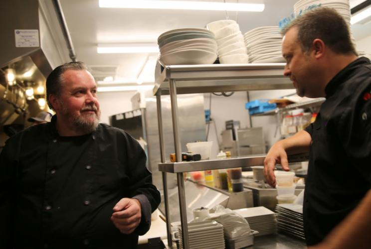 Chef Plum, right, and Nouveau Monde Wine Bar + Bistro co-owner Bill Towne talk in the restaurant's kitchen while the segment is filmed. (Bee Photo, Hallabeck)