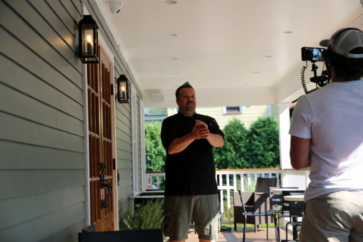 Chef Plum talks while Dan Fish of Full Send Productions films him on the back porch at Nouveau Monde Wine Bar + Bistro in Sandy Hook for an upcoming segment of <i>Restaurant Road Trip</i>. (Bee Photo, Hallabeck)