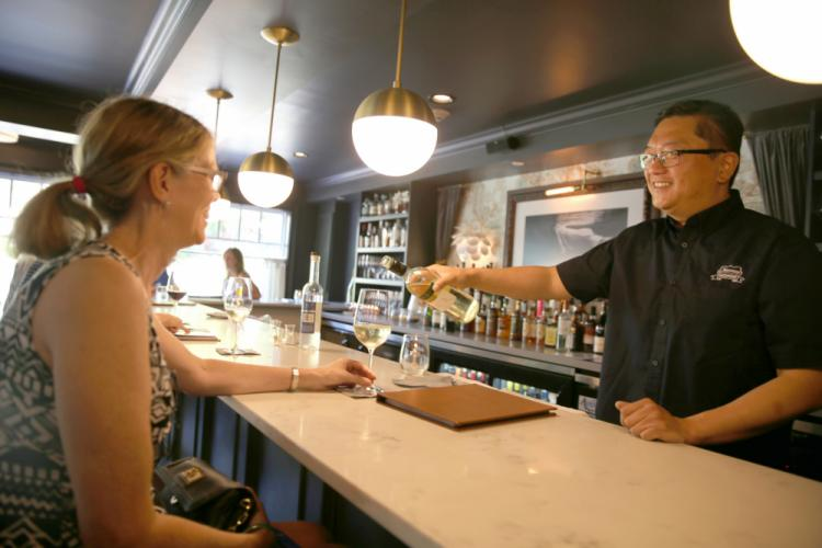 Nouveau Monde Wine Bar + Bistro Co-Owner Pete Chang pours resident Peg Bowers a glass of wine. Ms Bowers visited the Sandy Hook restaurant on August 1 after seeing a Facebook post announcing that  <i> Restaurant Road Trip </i>would be filmed there…