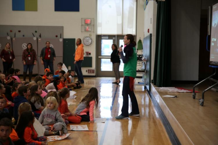 Sandy Hook School physical education teacher Jackie Lloyd, dressed in colorful attire to celebrated all of the teams in the school's food drive, spoke at the culminating assembly, held on November 22 to celebrate the school's food drive collection…