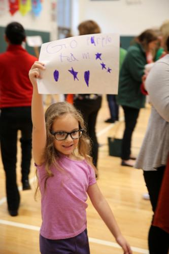 "Sandy Hook School student Penelope Goldie holds a sign reading, ""Go purple team,"" as she walked around the gymnasium with her team. (Bee Photo, Hallabeck)"