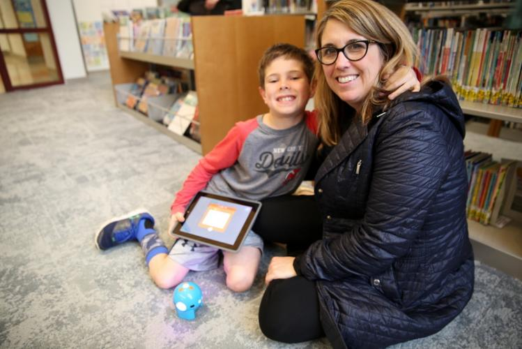 Sandy Hook Elementary School fourth grader Jack Meade and his mother, Michelle, pause for photo while working with a Dash & Dot robot, on the floor, at an April 24 Makerspace Night. (Bee Photo, Hallabeck)