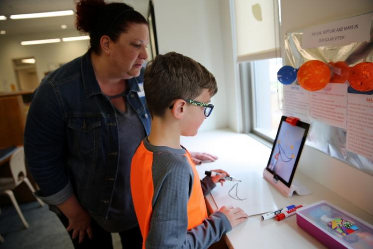 Dana Schicker and her third grade son, Collin, work together in one section of the Sandy Hook Elementary School library on April 25 to draw an image to connect dots shown on a tablet set up with an Osmo device. (Bee Photo, Hallabeck)