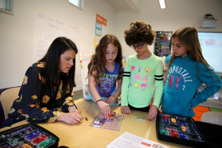 Sandy Hook Elementary School library/media specialist Katie Mauro works with students, from left, Serena Roberto, Madison Siksay, and Riley Quinn during a library class session at the school. The group used a Snap Circuits kit to create a…