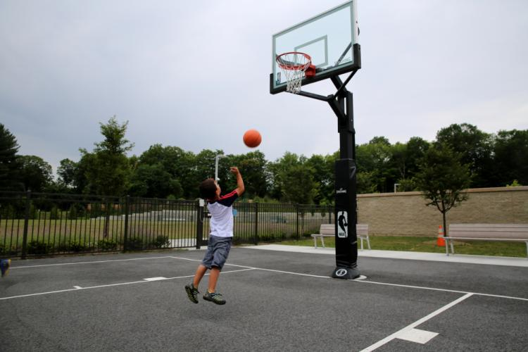 Antonio Puebla, 5, takes advantage of recess time at SMART Camp on July 6 to practice his basketball skills, outside Sandy Hook Elementary School. (Bee Photo, Hallabeck)