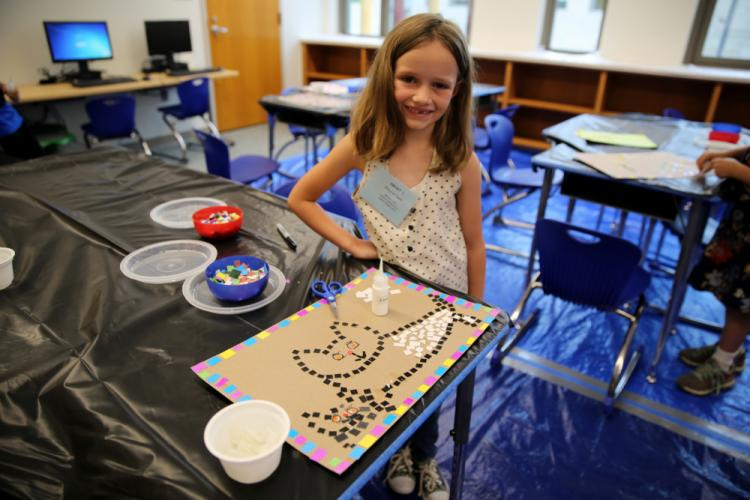 Shayna Clark stands next to a placemat she was working to create in the SMART Camp paper mosaics class. (Bee Photo, Hallabeck)