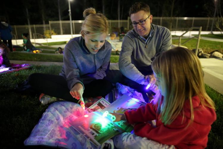 Kindergartener Elin Lohmann, front, using finger lights, reads with her mom, Tyra, and dad, Herb. The finger light flashlights were different colors and given out to participants at the event.  (Bee Photo, Hallabeck)