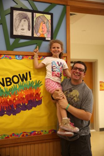 "Sandy Hook Elementary School second grade student Jocelyn Schwartz is lifted by her father Kris Schwartz so she can point out her ""Cubist Faces"" drawing on display at the school. (Bee Photo, Hallabeck)"