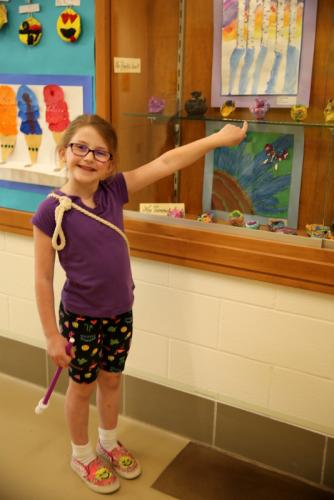 Sandy Hook Elementary School first grade student Makenzie Fregoe points at a pink and purple clay dog creation on display for the school's art show.  (Bee Photo, Hallabeck)