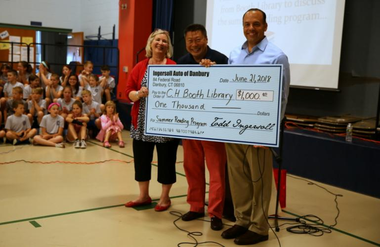 From left, C.H. Booth Library Children's Librarian Alana Bennison, State Senator Tony Hwang, and President and CEO of Ingersoll Automotive Todd Ingersoll stand together at a June 21 assembly at Hawley Elementary School, where Mr Ingersoll presented…