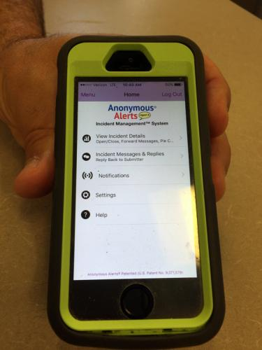 Director of Security Mark Pompano holds a phone showing the Anonymous Alerts app that can be used to report concerns anonymously.  (Bee Photo, Hallabeck)