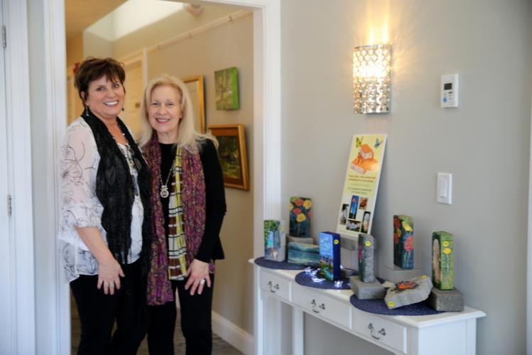 """During the opening reception for """"Spring in the AIR"""" on April 8, Avance Day Spa Owner Melanie Allen, left, and AIR Fine Art Gallery Curator Rosemary Rau stand near hand painted bricks on sale for the Team Brick fundraiser to raise money for the C.H…"""