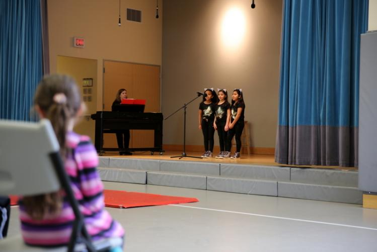 "St Rose of Lima School teacher Keri Salustri plays the piano as third graders, from left, Lela-Desta Liben, Cecilia Biasetti, and Natalene Villa sing the song ""Girl on Fire"" during the school's student talent show on February 1. (Bee Photo, Hallabeck)"