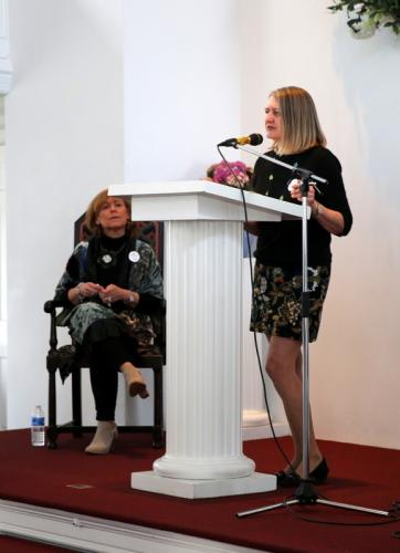 Risk A Verse coordinator artist Tracy Van Buskirk speaks at the podium near the opening of the April 8 event, while fellow coordinator Newtown Poet Laureate Lisa Schwartz looks on.  (Bee Photo, Hallabeck)