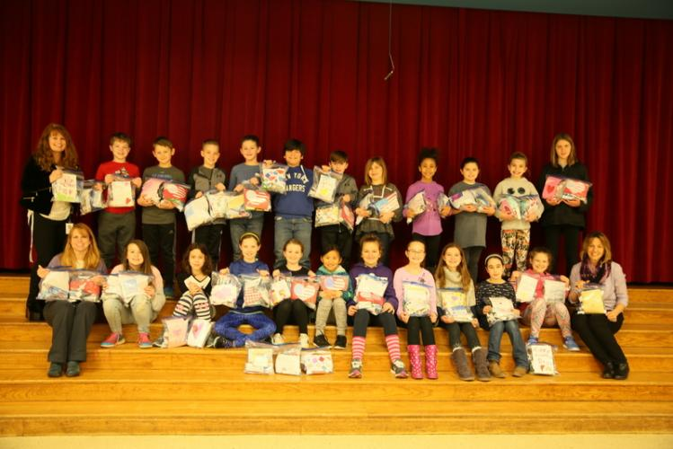 Head O' Meadow School Community Team (SCT) members hold completed care packages on January 23 that will be sent to Head O' Meadow secretary Laurie Martinelli's nephew and Marine Patrick Magee's unit. With the students are SCT advisors Rosemarie…