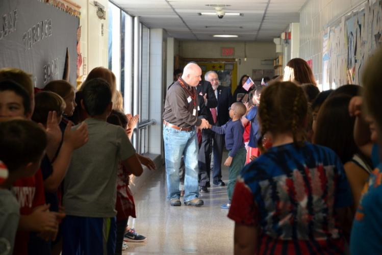 Visiting veterans at Middle Gate participate in a Walk of Honor after one assembly at the school for Veterans Day. Kevin Massett shakes fourth grade student Ethan Cameron's hand at the start of the line.  (Bee Photo, Hallabeck)
