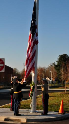 From left, US Marine Staff Sergeant Dustin Gill, Second Company Governor's Horse Guard Second Lieutenant Ken Fay, and US Marine Gunnery Sergeant Jason Reel worked together to raise the flag at Sandy Hook School for Veterans Day.  (Bee Photo, Hallabeck)