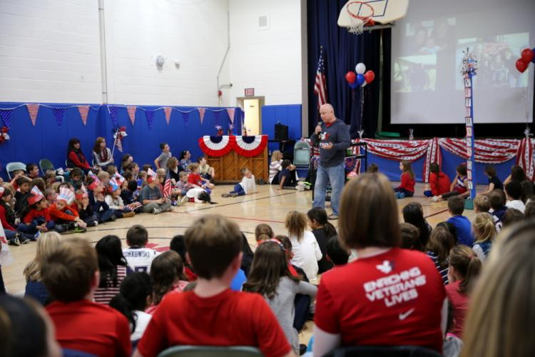Former Marine Kevin Massett speaks at Middle Gate Elementary School as his wife, Melissa and sons Charlie, center, and Billy look on.  (Bee Photo, Hallabeck)