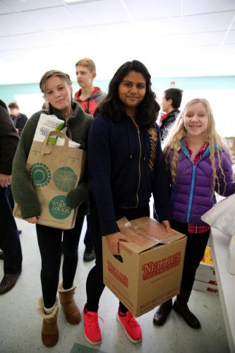 Fraser Woods Montessori School eighth graders, from left, Paige Comunale, Anish Kalaria, and Elisa Vittoria helped sort food donations at Newtown United Methodist Church on November 17 for the WIN Thanksgiving Basket Program. (Bee Photo, Hallabeck)