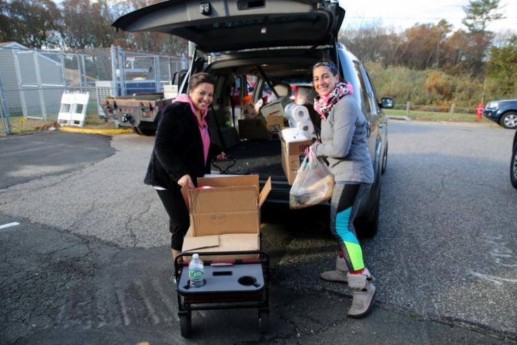 Middle Gate PTA President Amy Habboush, left, and PTA volunteer ChristineTisi help transfer donations for the WIN Thanksgiving Basket Program from the school into a car for the collection.  (Bee Photo, Hallabeck)