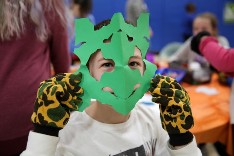 Middle Gate Elementary School fourth grader Sam Kennel holds up a mask he cut from paper while wearing gloves to simulate different motor skill levels at his school's Diversity Day on February 15. (Bee file photo)