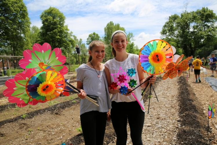 Reed sixth graders Ellie Meyer and Molly Lyddy hold pinwheels before installing them around The Victory Garden on May 24. The pinwheels were part of their cluster's effort to help rid The Victory Garden of groundhogs. (Bee file photo)