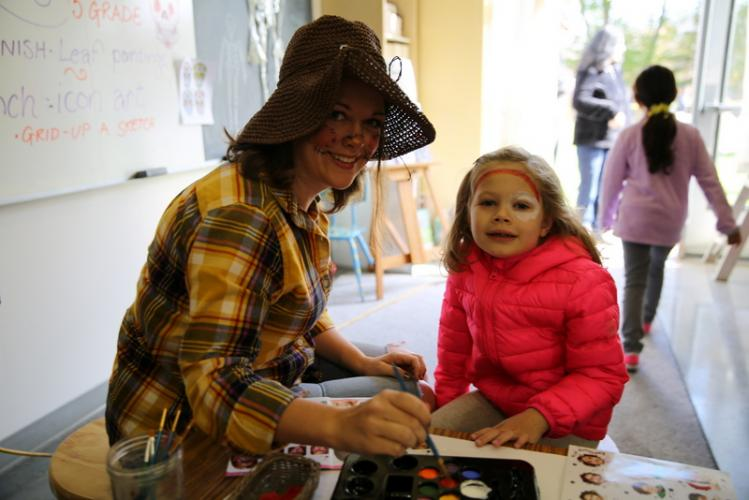 Fraser Woods Montessori School teacher Cynthia Wilson paints 4-year-old Riley Smith's face at the November 4 Fall Family Festival. (Bee file photo)