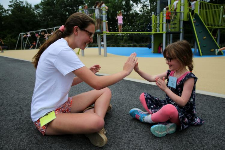 """SMART (Summer Music and Art) Camp intern Grace Larsen plays a game of """"Miss Mary Mack"""" with camper Adina Koldewyn, 6, during recess on July 6. (Bee Photo, Hallabeck)"""