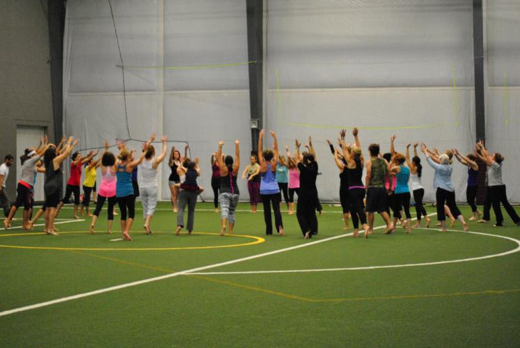 A group followed Newtown energy healer and yoga teacher Joanne Keane, not shown, through Journey Dance, a physical and emotional movement practice.
