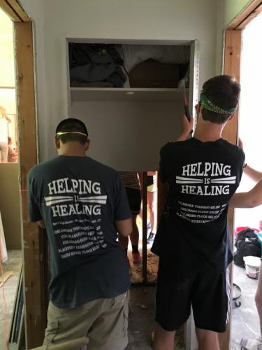 Wearing T-shirts that remind everyone of the mission of Ben's Lighthouse, Evan Song and Grant Larson replace drywall at a flooded home in Denham Springs in July.  (Rebecca Cosgrove photo)