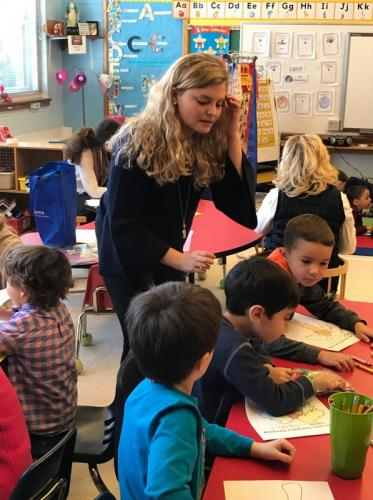 Grace Anne Herrick, a student at the University of Connecticut in Storrs, works with preschoolers at St Rose of Lima School on March 14 during a recent visit to the school. (Laura Moulder photo)