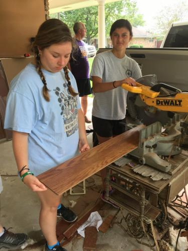 Grace Walter and Francesca D'Aprile were part of a crew that replaced flooring at a flooded home in Denham Springs.  (Rebecca Cosgrove photo)