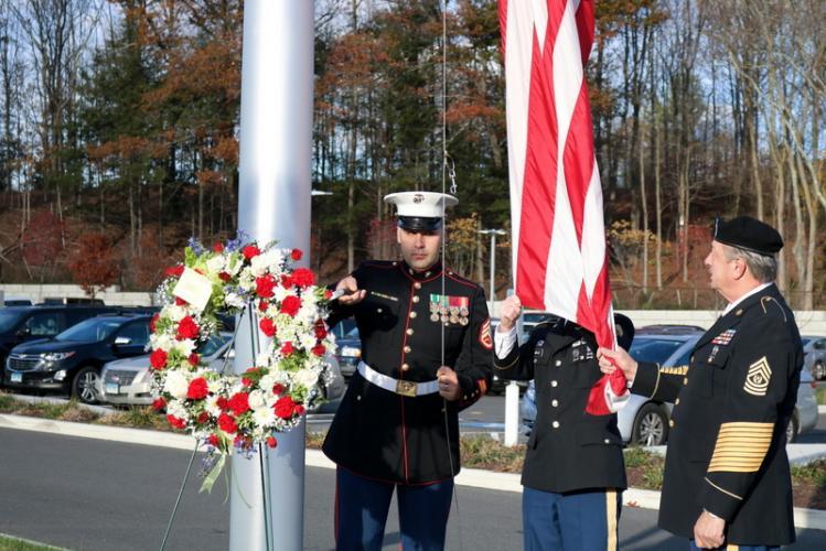 Veterans Dustin Gill, Tom Graze, Bill Skowronski, right, raise the flag at Sandy Hook School on November 10. (Mai Tran photo)